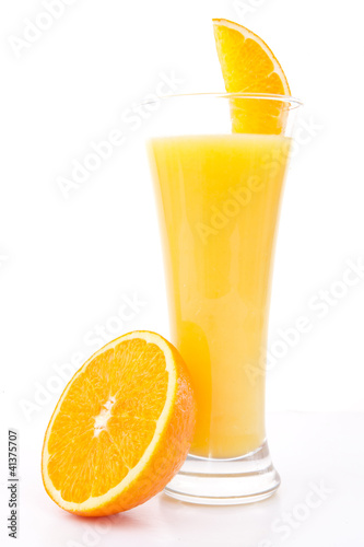 Half of am orange near a glass of orange juice