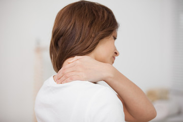 Brown-haired woman massaging her painful neck