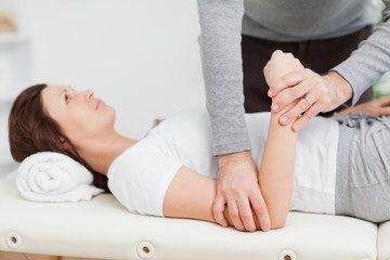Physiotherapist manipulating the arm of a peaceful woman