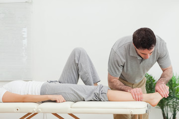 Chiropractor examining the foot of a woman