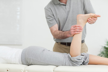 Woman lying forward while a physiotherapist examining her leg