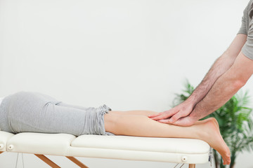 Close up of a masseur massaging the calves of a woman