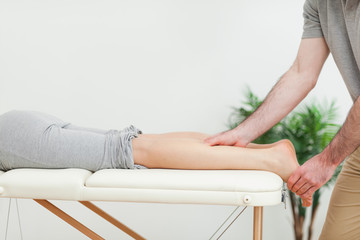 Woman lying while a masseur massaging the calves