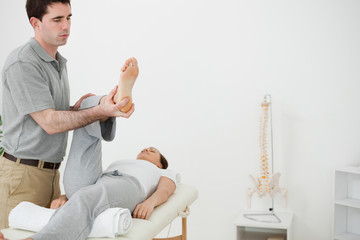 Brunette physiotherapist manipulating the leg of a woman