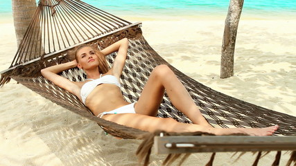Cute woman relaxing in a hammock at tropical beach