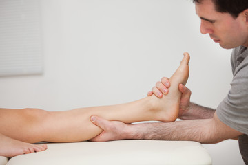 Serious physiotherapist holding the foot of a patient