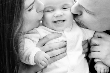 parents kissing smiling baby