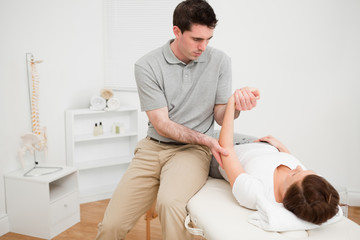 Physiotherapist holding the arm of a brunette woman