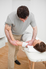 Osteopath working on a shoulder of a patient