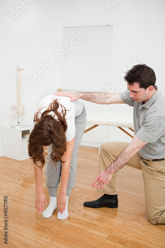 Doctor looking at a patient who is doing stretching exercises