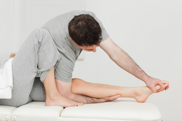Brunette osteopath stretching a foot