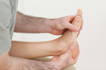 Osteopath holding the ball of a foot