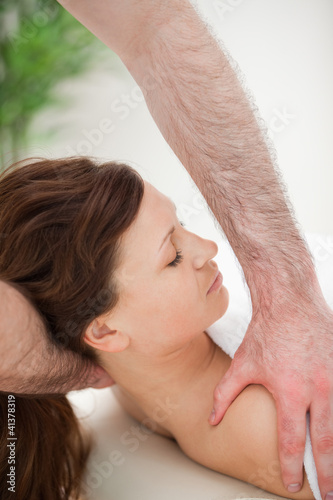 Therapist manipulating the neck of his patient while holding her