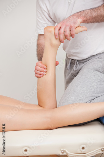 A doctor manipulating the ankle of his patient