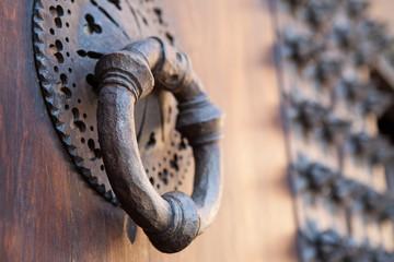 Aldaba de hierro forjado en puerta de madera antigua