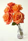elegant bouquet of golden roses in glas vase on bright backgroun