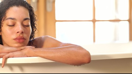 Portrait of mixed race woman in bathtub