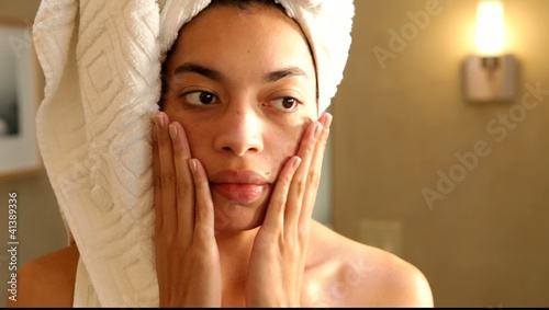 Mixed race woman applying lotion to her face