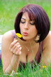 Beautiful woman plays with a flower in lush meadow