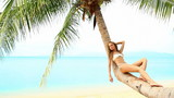 Relaxed woman resting on palm tree at the exotic beach