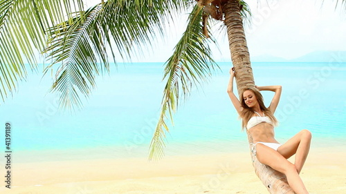 Sexy woman in bikini lying on palm tree at the beach