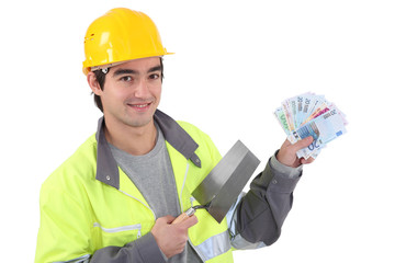 Tradesman holding a trowel and cash