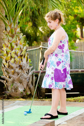 Young girl playing mini golf on putt putt course