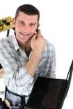 Handyman with a laptop and telephone