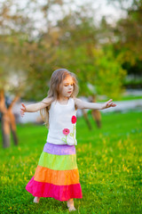 Adorable little girl dancing in the park