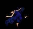 Caucasian beauty in blue dress floating in black
