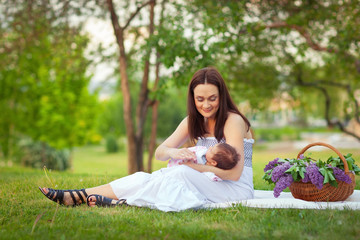 mother and baby resting in summer park with lilac bouquet