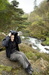 female hiker near river sheltering from the rain