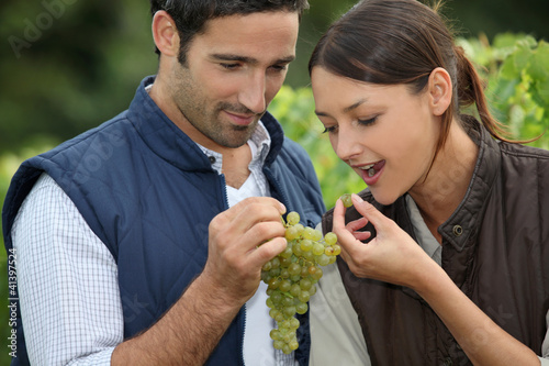 Winegrowers with bunch of grapes