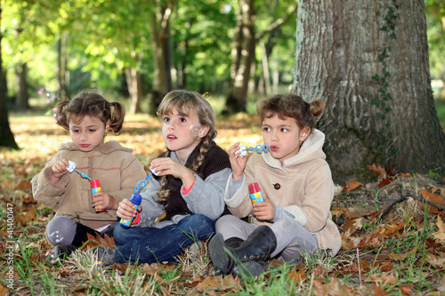 three little girls playing with soap bubble solutions