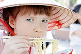 Young girl in hat eating spaghetti in restaurant