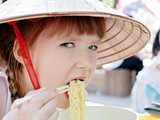 Little girl eating korean style spaghetti (ramen)