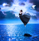 Fototapety Beautiful girl jumping into the blue night sky