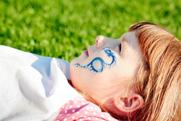 Portrait of a young girl with blue dragon on her face