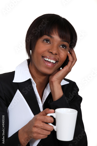 Businesswoman chatting on the phone with a hot drink