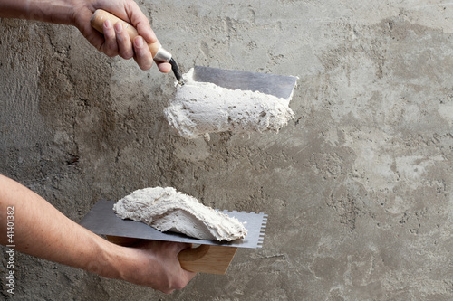 construction notched trowel and worker hands Poster
