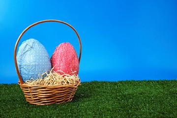 Easter eggs and wicker basket on garden