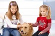 Little girls stroking dog smiling