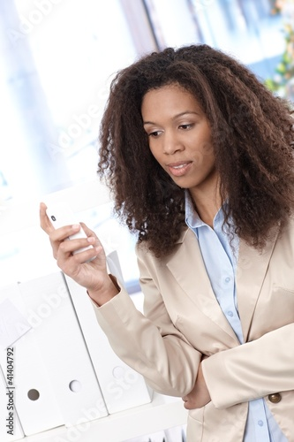 Afro businesswoman texting
