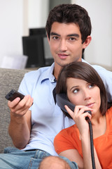 Couple relaxing in front room at home