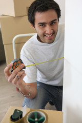 Man measuring wall