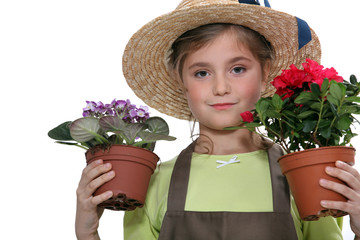 Little girl holding two plants in pots