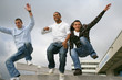 Three urban teenagers jumping down steps