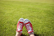Feet in sneakers in green grass