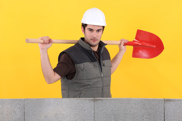 bricklayer holding shovel near concrete wall