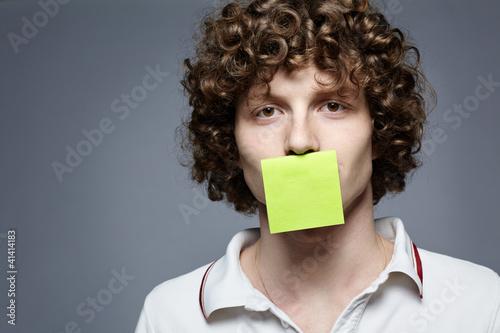 Young man with piece of paper covering his mouth